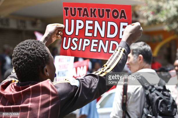 Opposition supporter carry a placard as they protest over the electoral reforms before the 26th October repeat presidential election antriot police...