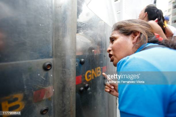Opposition supporter speaks with a National Guard member behind a barricade during a protest due to power, water and communication services faults in...