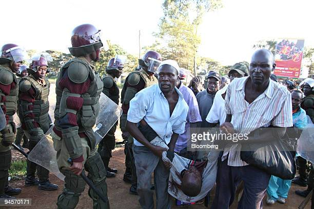 IMAGE CONTAINS GRAPHIC CONTENT Opposition supporters carry a man who was shot dead by police in the Kibera slums in Nairobi Kenya on Thursday Jan 17...