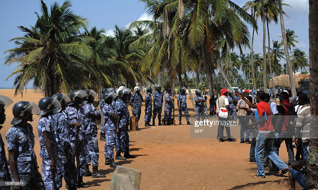 Opposition supporters (R) face police officers after trying to hold a sit-in near the Presidency in Lome on March 14, 2013 to protest a law which has given the HAAC (High Authority of Audiovisual and Communication) more power. The protesters were forced away from the Presidency by security forces and several journalists were reportedly injured by tear gas and rubber bullets. AFP PHOTO / Daniel Hayduk
