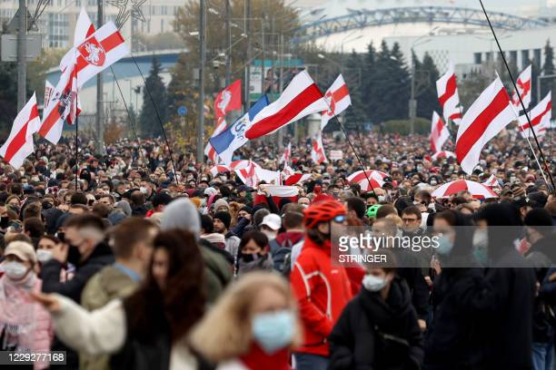 Opposition supporters hold former white-red-white flags of Belarus as they parade through the streets in Minsk, on October 25 on the final day of an...