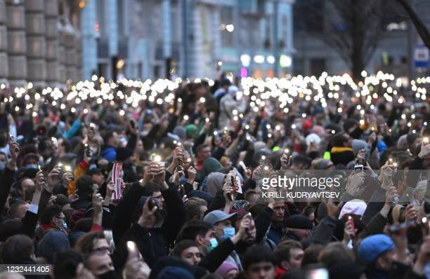 Opposition supporters hold their cell phones during a rally in support of jailed Kremlin critic Alexei Navalny, in central Moscow on April 21, 2021....