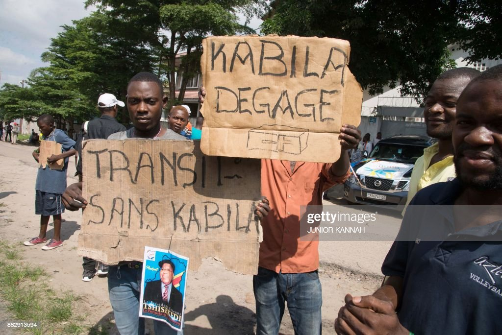 Opposition supporters hold up placards reading 'Kabila - get lost' and 'Transition without Kabila' as they demonstrate outside the residence of the Union for Democracy and Social Progress party (UD...
