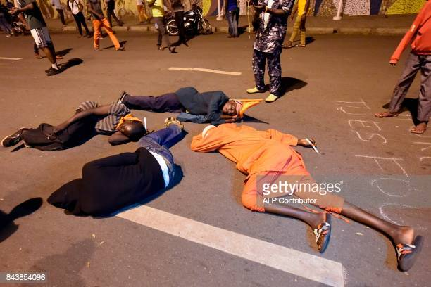 Opposition supporters lie on the road as they keep an allnight vigil to press for constitutional reform during antigovernment protests led by a...