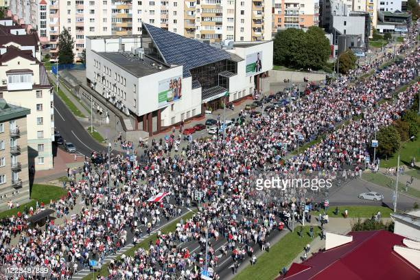 Opposition supporters parade through the streets during a rally to protest against the Belarus presidential election results in Minsk on September 13...