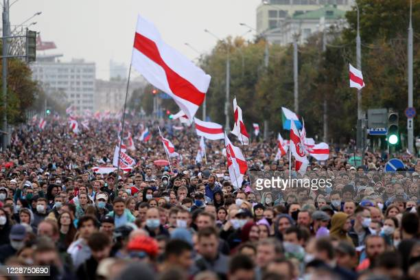 Opposition supporters parade through the streets during a rally to protest the country's presidential inauguration in Minsk on September 27, 2020. -...