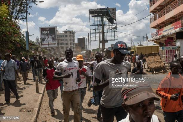 Opposition supporters run through the street in the Kawangware slum after a visit from presidential candidate Raila Odinga on October 29 2017 in...