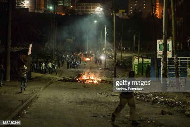 Opposition supporters stand around flaming roadblocks during unrest after election results were announced in the Mathare slum on October 30 2017 in...