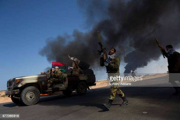 Opposition troops burn tires to use as cover during heavy fighting shelling and airstrikes near the main checkpoint near the refinery in Ras Lanuf as...
