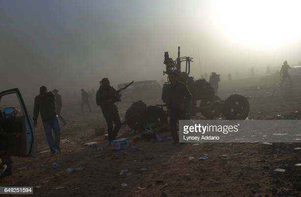 Opposition troops run in fear as they are hit with an airstrike about 100 meters from an opposition checkpoint near the refinery in Ras Lanuf Libya...