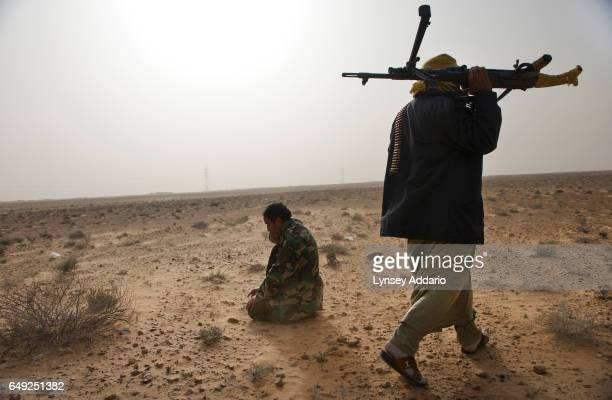 Opposition troops stop to pray along the road to Ras Lanuf as fighting continues between the opposition troops and those loyal to Muammar alGaddafi...