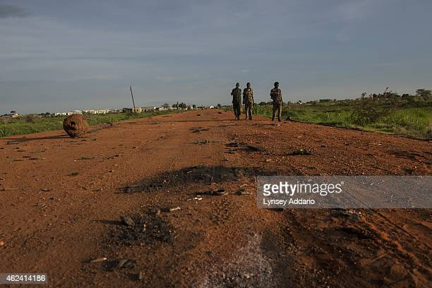 Opposition troops walk down a road littered with bullet casings and charred dirt the day after heavy fighting between opposition and government...