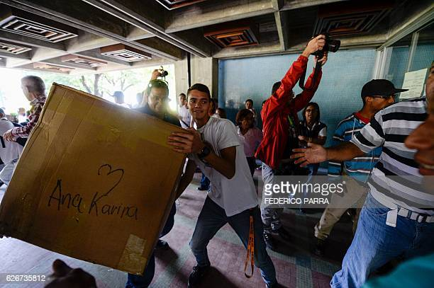 Opposition volunteers enter boxes with donations to the Dr Jose Gregorio Hernandez Hospital at Catia neighbourhood in Caracas on November 30 2016 /...