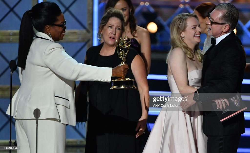 TOPSHOT - Oprah (L) presents the cast and crew of 'The Handmaid's Tale' the award for Outstanding Drama Series for 'The Handmaid's Tale' onstage during the 69th Emmy Awards at the Microsoft Theatre on September 17, 2017 in Los Angeles, California. / AFP PHOTO / Frederic J. Brown
