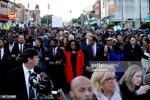 Oprah Winfrey along with members of the cast of Selma walk down Broad St towards the Edmund Pettus Bridge accompanied by thousands of participants in...