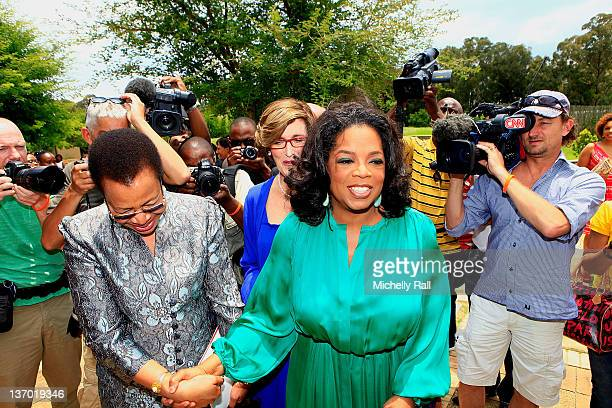 Oprah Winfrey leads Former President of South Africa Nelson Mandela's wife Graca Machel on her arrival at the inaugural graduation of the Class of...
