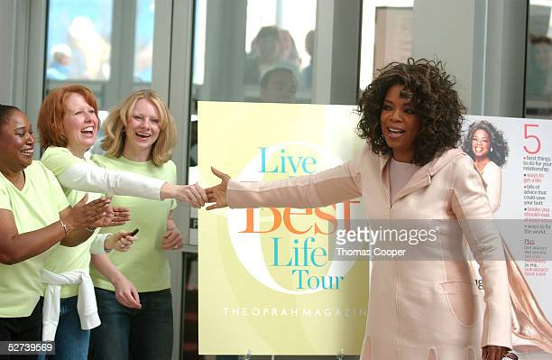 Oprah Winfrey touches the hand of one of the fans waiting at the door for her arrival during her Live Your Best Life Tour at the Colorado Convention...
