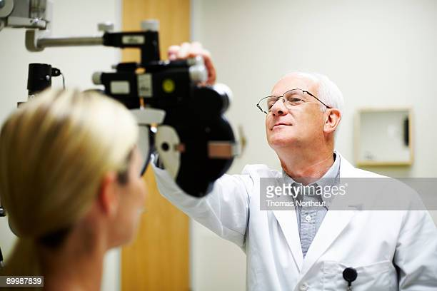 opthamologist measuring patient's eyesight - eye test stock pictures, royalty-free photos & images