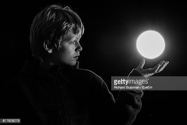 Optical Illusion Of Boy Levitating Illuminated Glowing Sphere Against Black Background