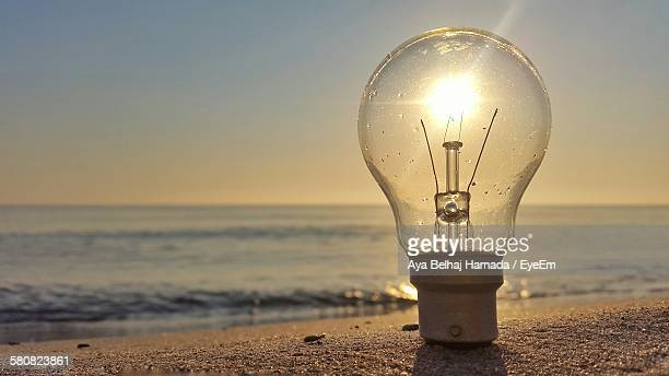 optical illusion of bright sun seen through light bulb on beach - optical illusion stock photos and pictures