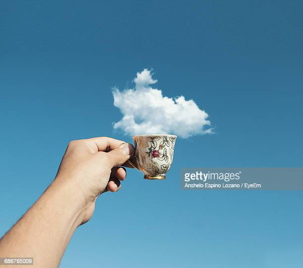 optical illusion of cropped hand holding cup with cloud against blue sky - optical illusion stock photos and pictures