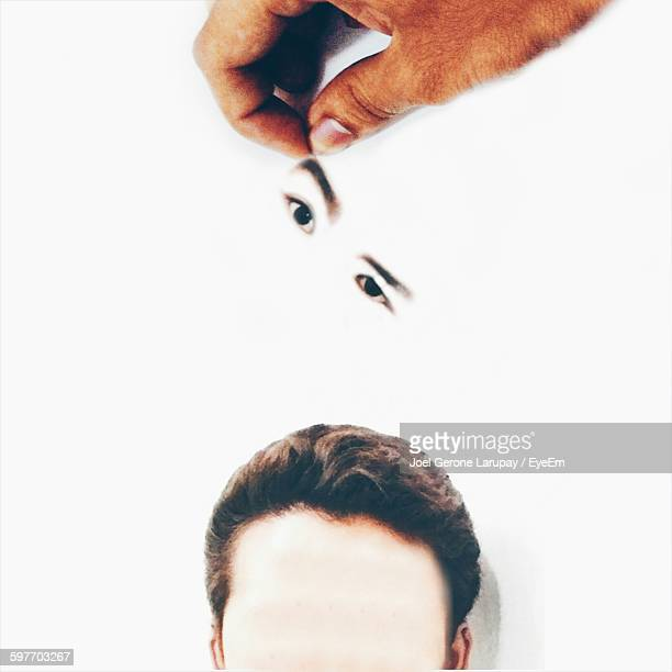 Optical Illusion Of Cropped Hand Holding Eyes Over Head Drawn On Paper