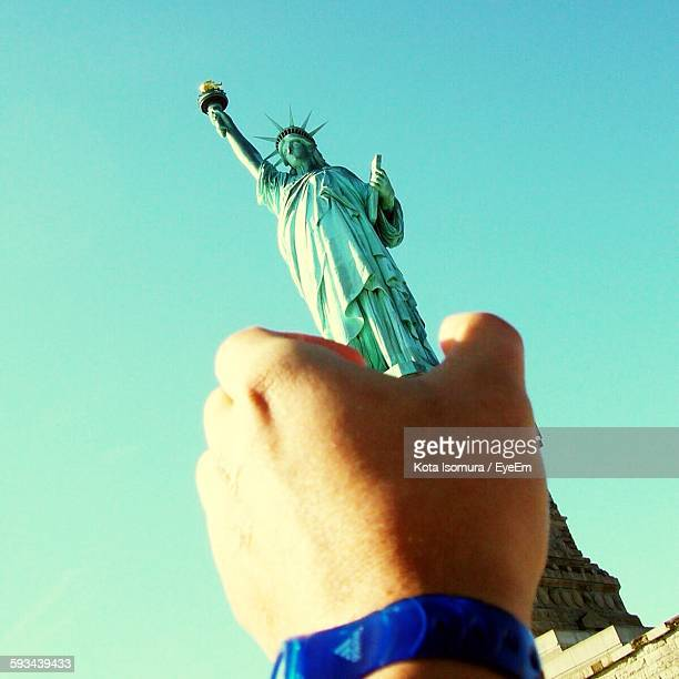 Optical Illusion Of Cropped Hand Holding Statue Of Liberty Against Clear Sky