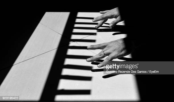 optical illusion of cropped hands playing piano on floor - optical illusion stock pictures, royalty-free photos & images