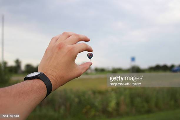 optical illusion of cropped man holding hot air balloon in sky - optical illusion stock photos and pictures