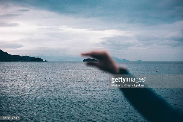 Optical Illusion Of Hand Holding Island Against Cloudy Sky