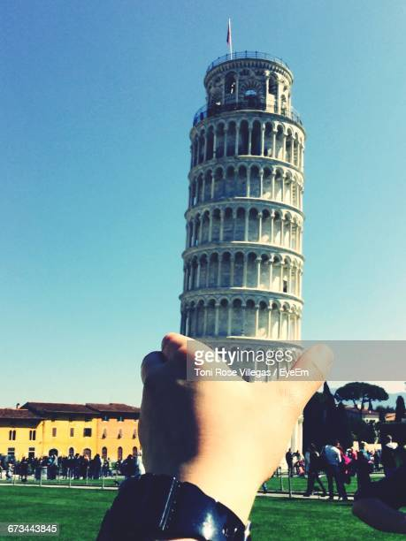 Optical Illusion Of Hand Holding Leaning Tower Of Pisa Against Sky