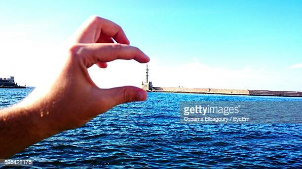 Optical Illusion Of Hand Holding Lighthouse At Harbor Against Sky
