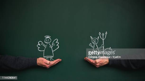optical illusion of hands holding evil and angel on blackboard - evil angel photos et images de collection