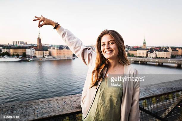 Optical illusion of happy female tourist holding building in city