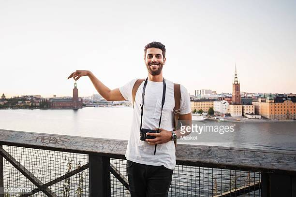 optical illusion of happy male tourist holding building in city against clear sky - photography themes stock pictures, royalty-free photos & images
