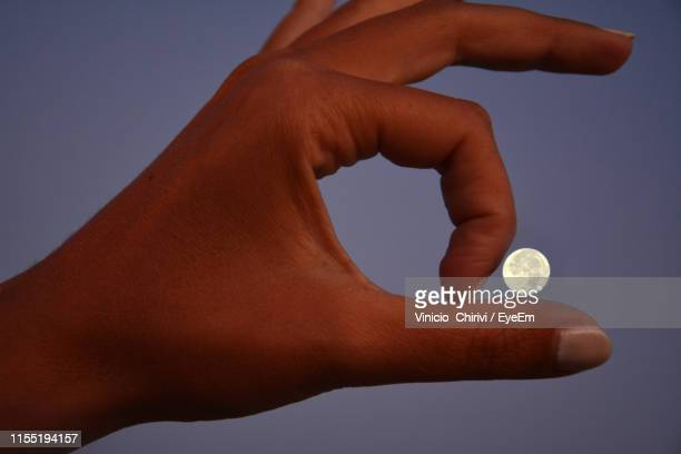 optical illusion of large hand by moon against sky at night - optical illusion stock pictures, royalty-free photos & images
