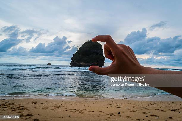 Optical Illusion Of Man Holding Rock At Beach Against Sky