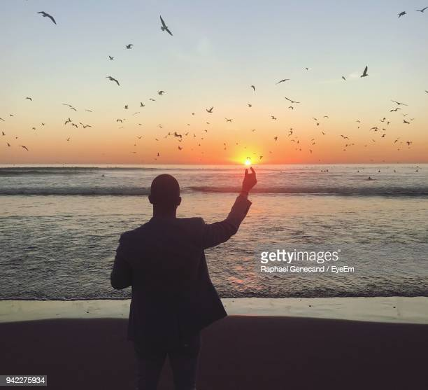 optical illusion of man holding sun at beach against orange sky - optical illusion stock photos and pictures