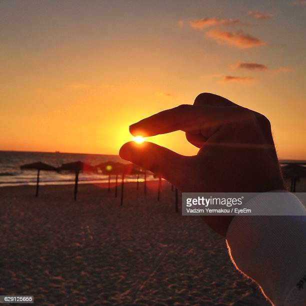 Optical Illusion Of Man Holding Sun At Beach