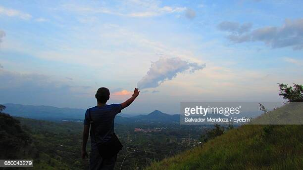 Optical Illusion Of Man Touching Cloud In Sky