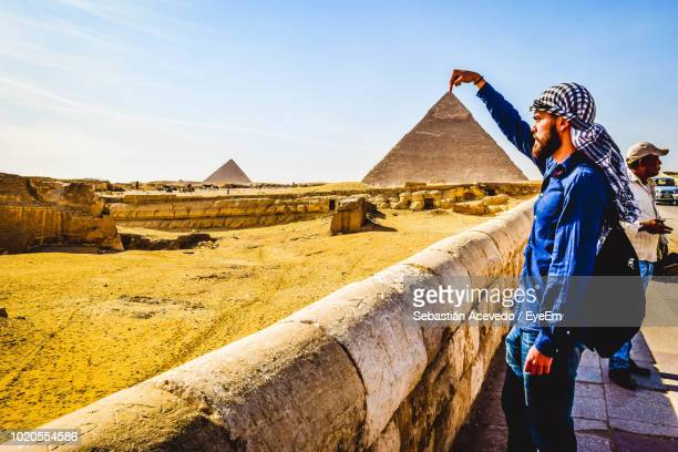 Optical Illusion Of Man Touching Pyramid Against Clear Sky