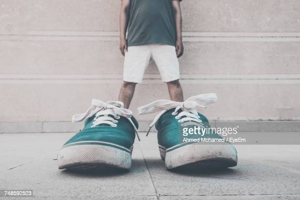optical illusion of man wearing green shoes against wall - optical illusion stock photos and pictures