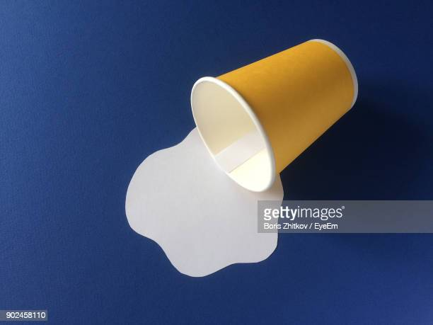 Optical Illusion Of Milk From Disposable Cup Over Blue Background