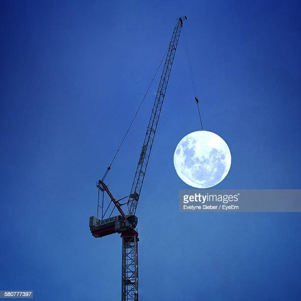 Optical Illusion Of Moon Hanging On Crane Against Sky At Dusk