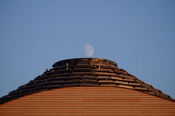 Optical Illusion Of Moon Over Building Against Clear Blue Sky