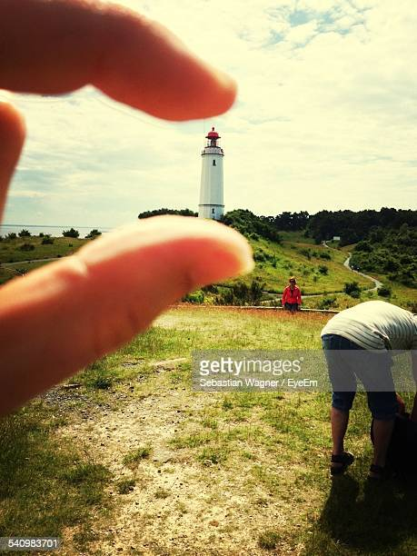 Optical Illusion Of Person Holding Dornbusch Lighthouse Against Cloudy Sky
