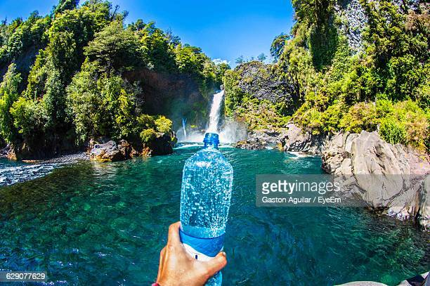 optical illusion of person holding waterfall in bottle - optical illusion stock photos and pictures