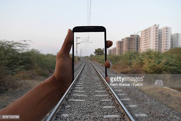 optical illusion of railroad tracks seen through mobile phone screen held by man - optical illusion stock photos and pictures