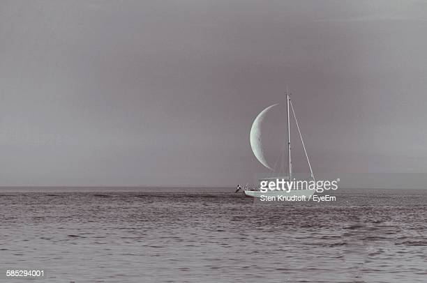 optical illusion of sailboat sailing on sea against half moon - optical illusion stock photos and pictures