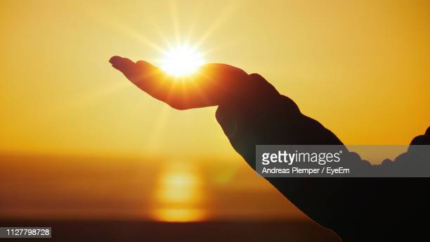 optical illusion of silhouette hand holding sun against sky during sunset - andreas solar stock pictures, royalty-free photos & images